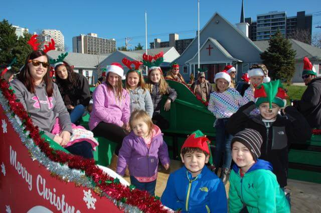 Sitting in the back of a float and waving is an important way to contribute to the Christmas Parade.
